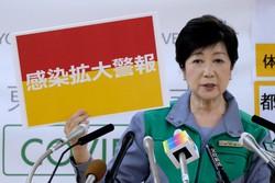 """Tóquio em alerta máximo por novos casos de coronavírus (Governadora de Tóquio, Yuriko Koike, segura uma placa que sinaliza """"alerta de propagação de infecção"""". Foto: Kazuhiro NOGI / AFP)"""