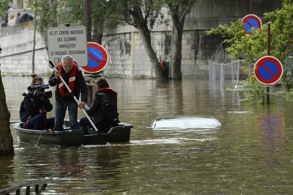 Jornalistas sobre um pequeno barco passam perto de um carro imerso em rua inundada ao longo do quai Louis Bleriot no 16º arrondissement em Paris. Foto:  AFP PHOTO / BERTRAND GUAY / AFP PHOTO / BERTRAND GUAY. -