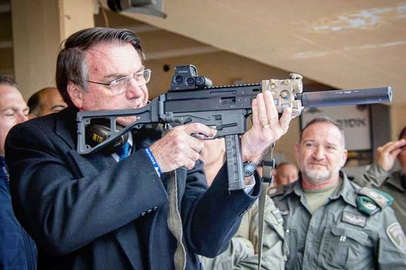 """FOTOS DO DIA  (Em viagem oficial a Israel, o presidente Jair Bolsonaro publicou nesta segunda-feira (1º) em uma rede social uma fotografia na qual está empunhando um fuzil. No post, ele defendeu a """"liberdade"""" de os cidadãos se armarem e criticou leis de desarmamento. Foto: Instagram / Bolsonaro.)"""