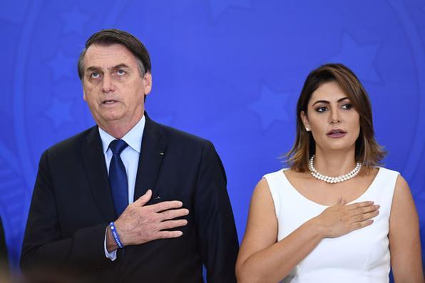 O presidente brasileiro Jair Bolsonaro (E) e a primeira-dama Michelle cantam o hino nacional durante a cerimônia de promoção dos novos oficiais gerais no Palácio do Planalto em Brasília, em 5 de abril de 2019. Foto: EVARISTO SA / AFP. -
