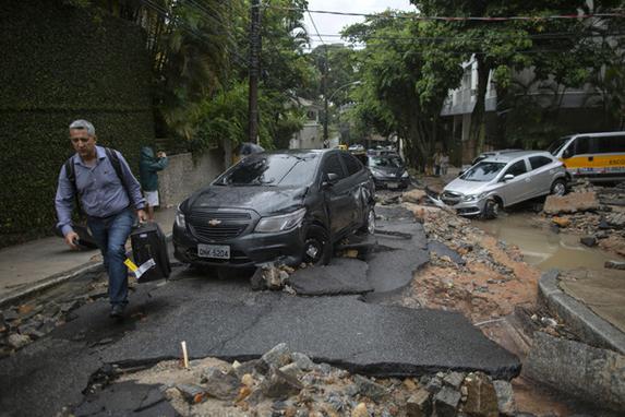 FOTOS DO DIA  (Um homem passa por carros danificados após fortes chuvas no bairro Jardim Botânico, no Rio de Janeiro, em 9 de abril de 2019. - As enchentes causadas por chuvas torrenciais mataram pelo menos três pessoas no Rio de Janeiro, disseram autoridades na terça-feira. Foto: MAURO PIMENTEL / AFP)