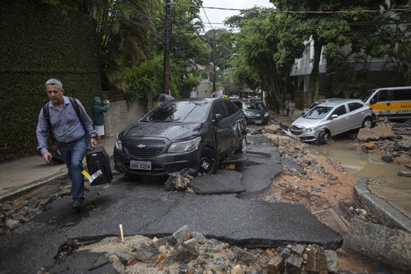 Um homem passa por carros danificados após fortes chuvas no bairro Jardim Botânico, no Rio de Janeiro, em 9 de abril de 2019. - As enchentes causadas por chuvas torrenciais mataram pelo menos três pessoas no Rio de Janeiro, disseram autoridades na terça-feira. Foto: MAURO PIMENTEL / AFP -