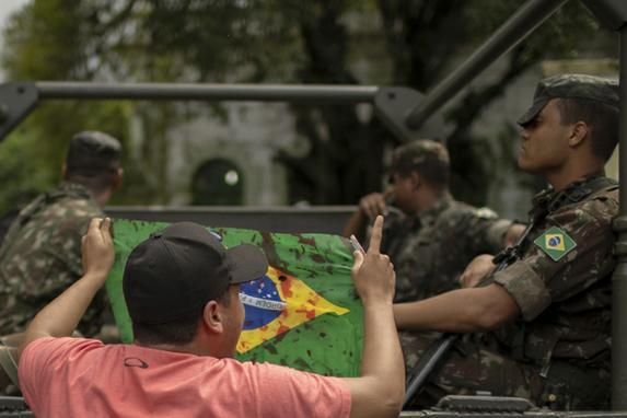 FOTOS DO DIA  (Amigos e parentes do músico brasileiro Evaldo dos Santos Rosa, que foi morto por uma unidade do exército quando atirou em seu carro por engano, seguram bandeiras nacionais brasileiras manchadas de vermelho - como sangue - durante um protesto no bairro da Vila Militar no Rio de Janeiro, Brasil em 10 de abril de 2019. Foto: Mauro Pimentel / AFP.)