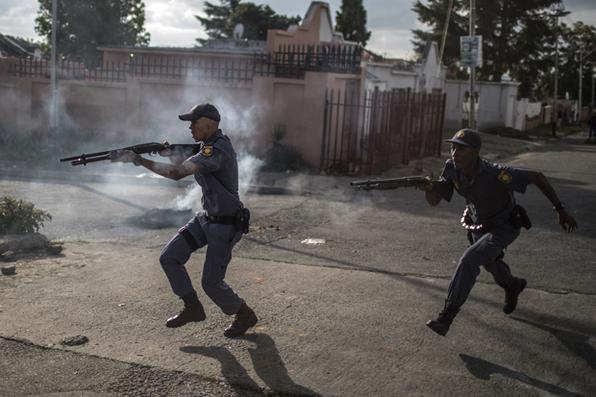 Policiais sul-africanos disparam balas de borracha enquanto perseguem manifestantes nas ruas de Johannesburgo, em 23 de abril de 2019, durante um protesto contra a falta de prestação de serviços ou necessidades básicas, como acesso a água e eletricidade, dificuldades de moradia e falta de manutenção de estradas públicas . Foto: MARCO LONGARI / AFP. -