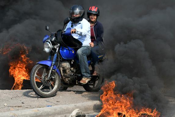 FOTOS DO DIA (Um homem e uma mulher andam de moto em meio a pneus queimando uma rua enquanto professores marcham durante uma greve nacional para protestar contra controversas reformas legislativas sobre saúde e educação, em Tegucigalpa, em 26 de abril de 2019. Foto: ORLANDO SIERRA / AFP.)