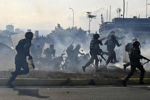 FOTOS DO DIA (Membros da Guarda Nacional Bolivariana, leais ao presidente venezuelano Nicolas Maduro, correm sob uma nuvem de gás lacrimogêneo depois de serem repelidos por guardas que apoiam o líder da oposição venezuelana Juan Guaido em frente à base militar de La Carlota, em Caracas, em abril. 30 de janeiro de 2019. Foto: Yuri CORTEZ / AFP.)
