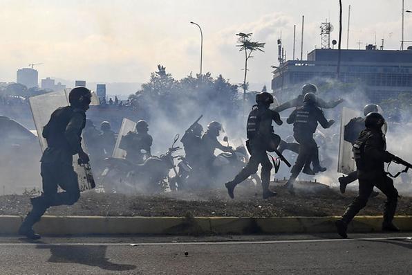 Membros da Guarda Nacional Bolivariana, leais ao presidente venezuelano Nicolas Maduro, correm sob uma nuvem de gás lacrimogêneo depois de serem repelidos por guardas que apoiam o líder da oposição venezuelana Juan Guaido em frente à base militar de La Carlota, em Caracas, em abril. 30 de janeiro de 2019. Foto: Yuri CORTEZ / AFP. -