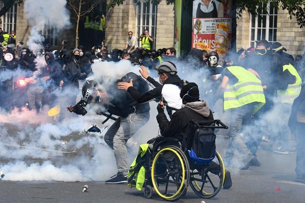 Um cinegrafista reage quando é atingido por uma bomba de gás lacrimogêneo enquanto um manifestante vai ajudá-lo durante confrontos com a polícia nos bastidores da manifestação anual do Dia de Maio em Paris em 1 de maio de 2019. Foto: Alain Jocard / AFP. -