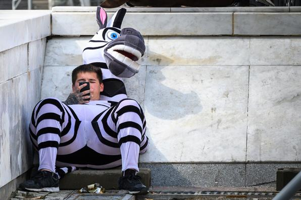 Um homem novo vestido como uma zebra descansa em Moscovo central em 10 de maio de 2019. - Moscovo goza de uma onda de calor, enquanto o resto da Europa se esforça com o tempo frio. (Foto Mladen ANTONOV / AFP). -