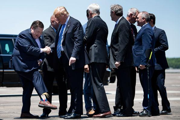 O tenente-governador da Louisiana, Billy Nungesser, mostra ao presidente dos EUA Donald Trump suas meias depois que o presidente chega ao Aeroporto Internacional Chennault em 14 de maio de 2019, em Lake Charles, Louisiana. (Foto de Brendan Smialowski / AFP). -