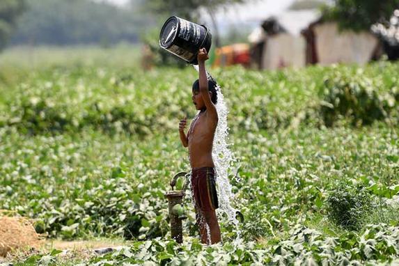 FOTOS DA CATEDRAL DE NOTRE - DAME (Menino indiano despeja água em si mesmo enquanto tenta se refrescar em meio a temperaturas elevadas em Nova Delhi, em 29 de maio de 2019. (Foto de Money SHARMA / AFP).)