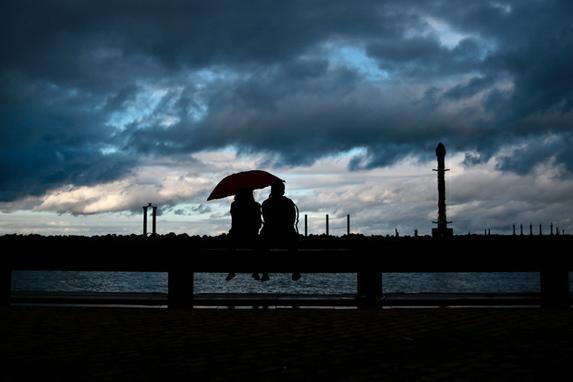 FOTOS DO DIA (Casal se protege da chuva no Marco Zero - Recife Antigo, nesta Sexta (31). Foto: Tarciso Augusto / Esp. DP Foto.)