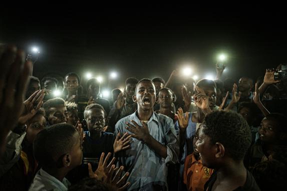 FOTOS DA SEMANA (As pessoas cantam slogans quando jovem recita um poema sobre revolução, iluminado por telefones celulares, antes do diálogo direto da oposição com pessoas em Cartum em 19 de junho de 2019. Foto: Yasuyoshi CHIBA / AFP)