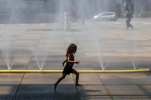 FOTOS DO DIA  (Uma menina corre através de água pulverizada de um cano na Praça Praterstern em Viena, em 25 de julho de 2019. - Os meteorologistas prevêem novas altas de temperatura na Europa Ocidental atingidas por outra onda de calor estabelecendo novos recordes de temperatura. (Foto de ALEX HALADA / AFP) )