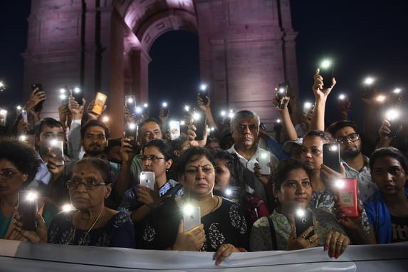FOTOS DO DIA  (Ativistas sociais indianos usam sua luz móvel enquanto participam de uma manifestação de solidariedade em frente ao monumento India Gate para a vítima de estupro Unnao em Nova Delhi, em 29 de julho de 2019. - Uma adolescente indiana que acusou um político sênior de estupro está lutando por ela vida depois de ser gravemente ferido em um acidente em 28 de julho de 2019, que matou dois parentes, levantando suspeitas de jogo sujo. (Foto de SAJJAD HUSSAIN / AFP))