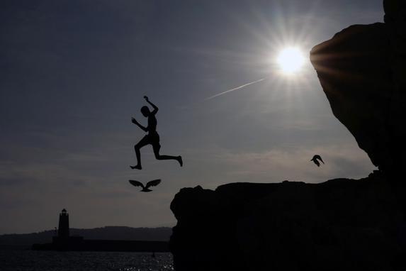 FOTOS DO DIA (Um jovem pula no Mar Mediterrâneo na cidade de Nice, na Riviera Francesa, em 31 de julho de 2019. (Foto de VALERY HACHE / AFP).)