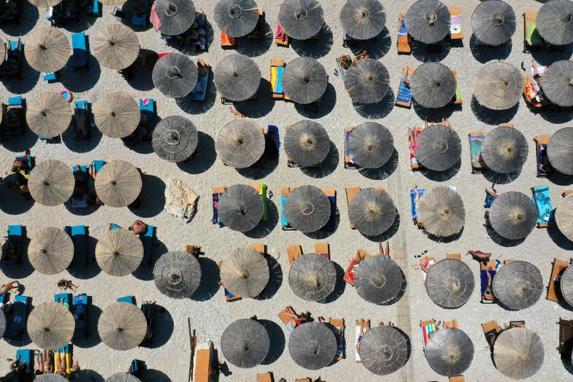 FOTOS DO DIA  (Esta vista aérea tomada em 6 de agosto de 2019, mostra turistas e guarda-sóis na praia de Llaman, perto da cidade de Himare. - As condições do tempo quente dos últimos dias na Albânia viram as temperaturas atingirem um pico de 37 graus Celsius. (Foto de Gent SHKULLAKU / AFP).)