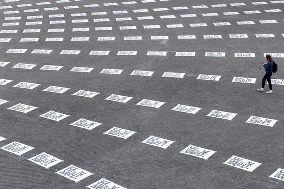 """FOTOS DO DIA - 06 de Setembro de 2019 (Uma mulher caminha por uma praça coberta de pôsteres com a frase """"Justiça para Steve"""" na Place Royale, na cidade francesa de Nantes, no dia 06 de setembro de 2019. - Os cartazes se referem a Steve Maia Canico, um francês de 24 anos, 24 anos, francês de um ano que desapareceu em junho passado depois de cair no rio após uma batida policial durante um festival de música. (Foto de Sebastien SALOM-GOMIS / AFP))"""
