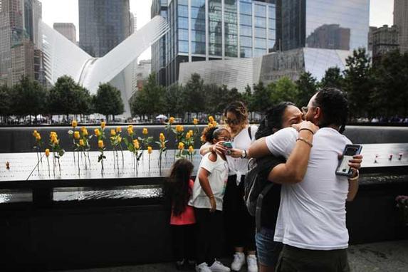FOTOS DO DIA - 11 de Setembro de 2019 (Os filhos de Flowers Elena Ledesma, morta em 11 de setembro enquanto trabalhava no World Trade Center como coordenadora de manutenção da Marsh & McLennan, se abraçam no Memorial Nacional de 11 de setembro durante uma cerimônia de comemoração pela manhã para as vítimas dos ataques terroristas Dezoito anos após o dia 11 de setembro de 2019 na cidade de Nova York. Em todo o país, estão sendo realizados serviços para lembrar as 2.977 pessoas mortas em Nova York, no Pentágono e em um campo na Pensilvânia rural. Foto: Spencer Platt / Getty Images / AFP.)