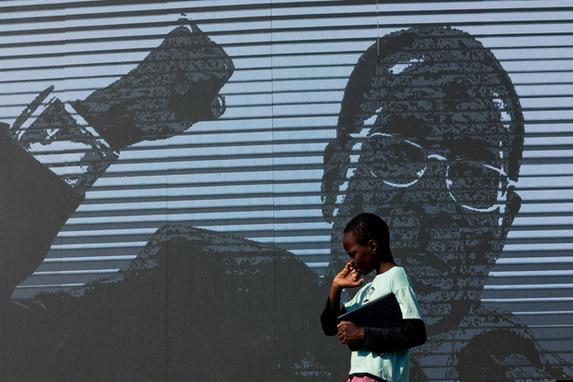 FOTOS DO DIA - 16 de Setembro de 2019 (Um menino passa por uma imagem digital do ex-presidente do Zimbábue Robert Mugabe enquanto seu corpo está no estado em Murombedzi Growth Point, cerca de 107 km a noroeste de Harare, Zimbábue, em 16 de setembro de 2019, quando as pessoas tiveram a oportunidade de ver O corpo de Mugabe uma semana após sua morte. - Os restos mortais do ex-presidente do Zimbábue Robert Mugabe foram levados para sua aldeia em 16 de setembro, disse um membro da família, enquanto seu enterro final é preparado em cerca de um mês. Mugabe morreu há uma semana, aos 95 anos, em Cingapura, quase dois anos depois de ter sido deposto em um golpe de 2017 que terminou quase quatro décadas de regime cada vez mais autocrático. Foto: Jekesai NJIKIZANA / AFP.)