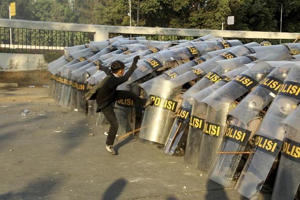 Um manifestante ataca uma linha policial durante uma manifestação em Jacarta, em 30 de setembro de 2019. - A polícia de choque disparou gás lacrimogêneo contra manifestantes que atiravam pedras, quando novos protestos irromperam na Indonésia em 30 de setembro, desencadeados por uma série de reformas legais divergentes, incluindo a proibição de sexo conjugal e enfraquecendo a agência anti-enxerto. Foto: Dany Krisnadhi / AFP. -