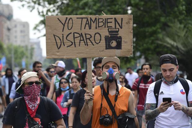 FOTOS DO DIA - 25 de Outubro de 2019 (Um homem segura uma placa que diz 'eu também atiro' durante uma manifestação após uma semana de violência nas ruas de Santiago, em 25 de outubro de 2019. - Manifestações contra uma subida no preço dos bilhetes de metrô na capital do Chile explodiram em violência em 18 de outubro, desencadeando ampliação de protestos sobre custo de vida e desigualdade social. (Foto de Martin BERNETTI / AFP) )