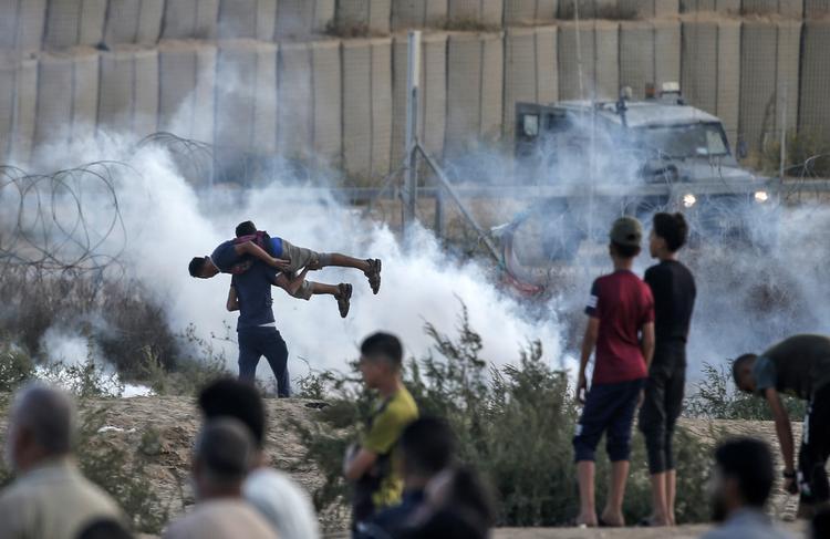 FOTOS DO DIA - 01 de Novembro de 2019 (Um manifestante palestino leva um amigo ferido em meio a confrontos com forças israelenses durante uma manifestação ao longo da fronteira com Israel a leste de Bureij, na faixa central de Gaza, nesta sexta - feira (01). Foto: MAHMUD HAMS / AFP.)
