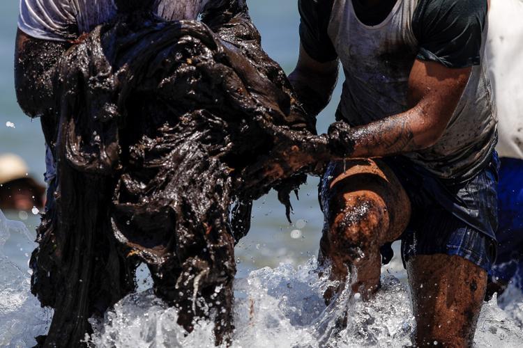 OLÉO NO LITORAL - MELHORES FOTOS (Homens são vistos retirando manchas de oléo do mar, que foram encontradas na praia do Paiva no Cabo de Santo Agostinho, voluntários participaram da retirada do oléo na costa, no dia 21/10/2019. Foto : Leandro  de Santana / Esp.DP FOTO.)