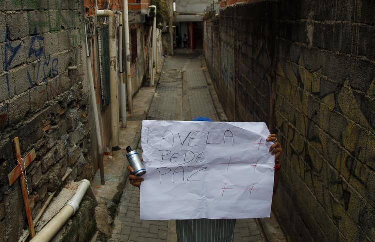 FOTOS DO DIA - 02 de Dezembro de 2019 (Um homem segura um cartaz que diz `` A favela pede paz '' em um beco em Paraisópolis, sul de São Paulo, Brasil, nesta segunda feira (02), depois que nove pessoas morreram após uma batida policial. - Pelo menos nove pessoas foram pisoteadas até a morte e outras duas ficaram feridas no início do domingo, depois de uma operação policial em um bairro pobre de São Paulo, informaram as autoridades locais. Foto: Miguel SCHINCARIOL / AFP.)