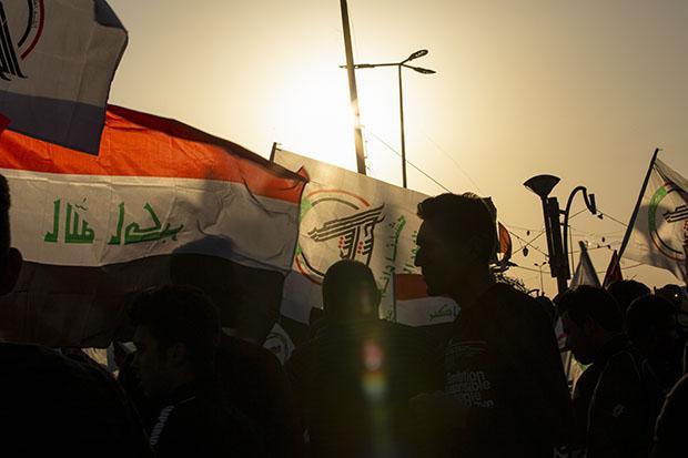 FOTOS DO DIA - 30 de Dezembro de 2019 (Os iraquianos agitam a bandeira nacional e as bandeiras da rede armada Hashed Al-shaabi na cidade de Basra, no sul, em 30 de dezembro de 2019, durante uma manifestação para denunciar os ataques da noite anterior por aviões dos EUA em várias bases pertencentes às brigadas do Hezbollah perto de Al-Qaim , um distrito iraquiano na fronteira com a Síria. - Ataques aéreos dos EUA contra um grupo pró-Irã no Iraque teriam matado pelo menos 25 combatentes, provocando raiva em um país envolvido em crescentes tensões entre Teerã e Washington. Foto de Hussein FALEH / AFP)