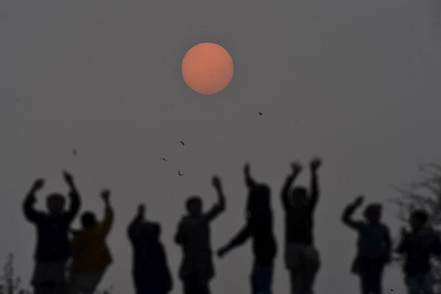 FOTOS DO DIA - 31 de Dezembro de 2019 (As crianças brincam durante o último pôr do sol de 2019, em Lahore, em 31 de dezembro de 2019. Foto: Arif ALI / AFP )