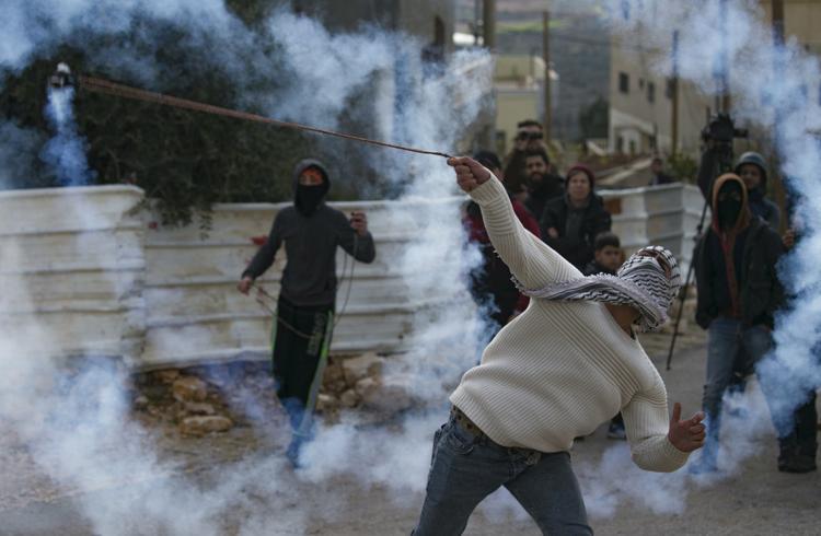 FOTOS DO DIA - 10 de Janeiro de 2020 (Um manifestante palestino usa um estilingue para devolver um cartucho de gás lacrimogêneo às forças israelenses durante os confrontos com eles, após um protesto semanal contra a expropriação de terras palestinas por Israel, na aldeia de Kfar Qaddum, na Cisjordânia ocupada em 10 de janeiro de 2020. Foto: JAAFAR ASHTIYEH / AFP.)