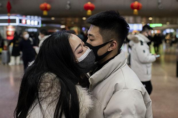 FOTOS DO DIA - 24 de Janeiro de 2020 (Um casal, usando máscaras protetoras, se despede durante as férias do Ano Novo Lunar, na Estação Ferroviária Oeste de Pequim, em Pequim, em 24 de janeiro de 2020. - As autoridades chinesas expandiram rapidamente um gigantesco esforço de quarentena para conter um contágio mortal em 24 de janeiro para 13 cidades e 41 milhões de pessoas, já que moradores nervosos foram checados por febres e o número de mortos subiu para 26. Foto: NICOLAS ASFOURI / AFP)