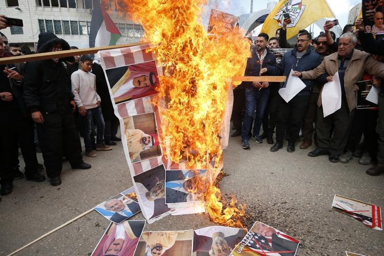 FOTOS DO DIA - 30 de Janeiro de 2020 (Manifestantes raivosos palestinos retratam o rei Hamad al-Khalifa (E) do Bahrein, o xeque Mohammed bin Rashid al-Maktoum (C), o primeiro ministro e governante de Dubai dos Emirados Árabes Unidos, bem como o novo governante real de Omã, Haitham bin Tariq (D) durante um protesto contra uma proposta de plano de paz dos EUA no centro da cidade palestina de Hebron na Cisjordânia ocupada por Israel em 30 de janeiro de 2020. Foto: HAZEM BADER / AFP.)