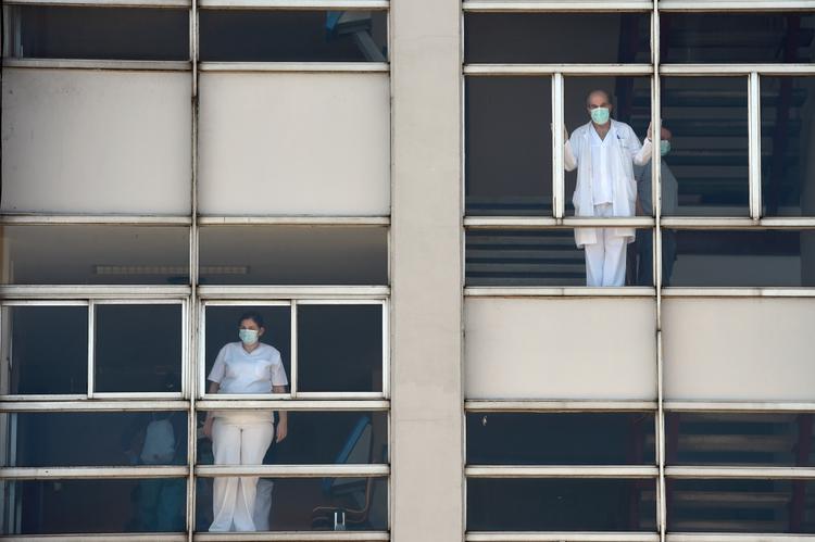 CORONAVÍRUS: Veja as fotos do dia 26 de Março de 2020 (Os profissionais de saúde que lidam com a nova crise de coronavírus olham através das janelas do Hospital Universitário de Coruna, no noroeste da Espanha, em 26 de março de 2020. O número de mortes por coronavírus na Espanha subiu acima de 4.000 hoje, mas o aumento nas fatalidades e nas novas infecções diminuiu, deixando as autoridades esperançosas um bloqueio nacional está começando a coibir a propagação da doença. Um total de 655 mortes foram registradas no país nas últimas 24 horas, elevando o número para 4.089, informou o Ministério da Saúde. (Foto de MIGUEL RIOPA / AFP))
