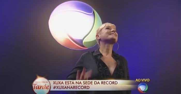Apresentadora assinou o contrato ao lado do vice-presidente artístico e de programação da emissora. Crédito: Facebook/Reprodução