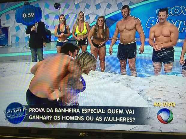 Cantor Léo Santana segura campeã de halterofilismo na hora de pegar os sabonetes. Créditos: Record/Reprodução