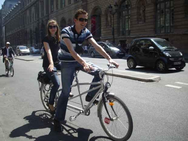 """Casal anda de bicicleta por Paris. Agora eles poderão """"furar"""" semáforos vermelhos pela cidade para melhorar o trânsito. (Foto: Domínio público)"""