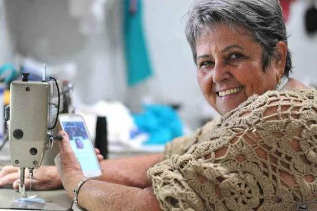 """A costureira Gilda Rodrigues usa a internet para se comunicar com a família e os clientes: """"Meu celular fica o dia todo comigo, aqui do meu lado"""". Foto: Helio Montferre/Esp.CB/D.A Press"""