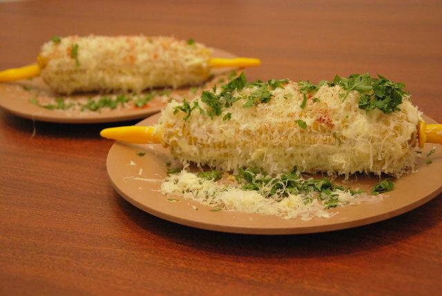 Milho Cordel (espiga cozida coberta com cream cheese, raspas de parmesão, coentro e páprica defumada), pela chef Miau Caldas. Foto: Cordel Cafés/Divulgação