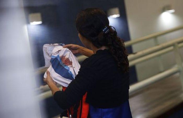 Bruna, mãe do adolescente Marcos Vinicius da Silva, segura camisa da escola que ele usava quando foi assassinado Foto: Fernando Frazão/Agência Brasil