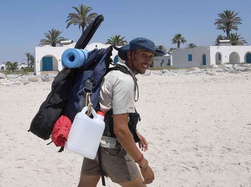 """Mohamed Ossama iniciou o projeto """"300 Quilômetros"""" em Mahdia (leste) e vai terminá-lo na praia de Soliman, a 40 km da cidade de Túnis, após ter limpado tanto praias muito frequentadas quanto as mais escondidas. Foto: Fethi Belaid AFP"""