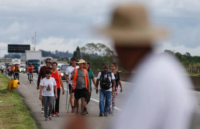 Milhares de romeiros caminham a pé pelo acostamento da Rodovia Presidente Dutra até o Santuário de Nossa Senhora Aparecida; na imagem, os peregrinos em Pindamonhangaba  Foto: Werther Santana/Estadão