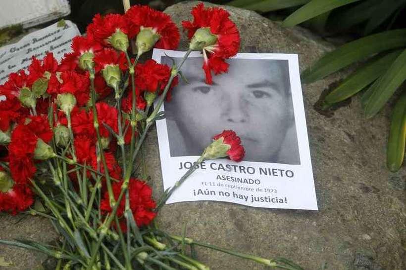 Pessoas colocam flores nos túmulos de pessoas mortas no golpe, durante a comemoração do 44º aniversário do golpe militar liderado pelo general Augusto Pinochet. Foto: AFP / CLAUDIO REYES