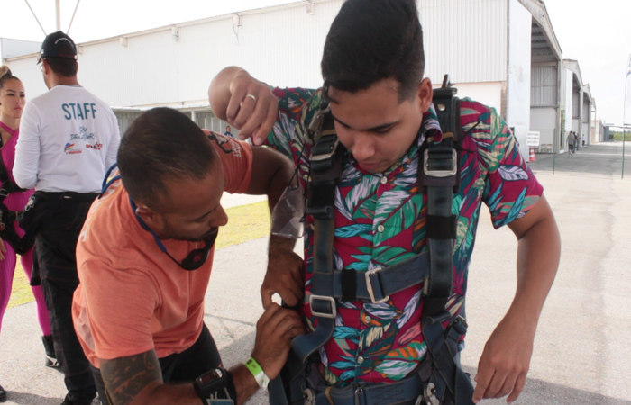 Instrutor Bruno Cury colocando o macacão de segurança no repórter Samuel Calado. Foto: Jefferson Belarmino/Cortesia