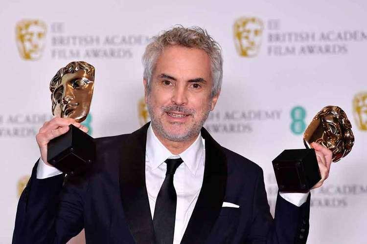 O mexicano Alfonso Cuarón exibe as estatuetas de melhor filme e diretor, em Londres. Foto: Ben Stall/AFP