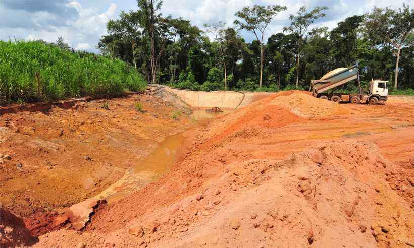 Caminhões depositam material na base da contenção, de onde água escoa. Foto: Gladyston Rodrigues/EM/DA Press