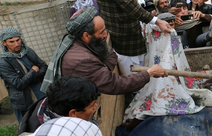Afegãos cobrem os corpos de crianças mortas nos bombardeios na província de Kunduz em 23 de março de 2019. Foto: AFP