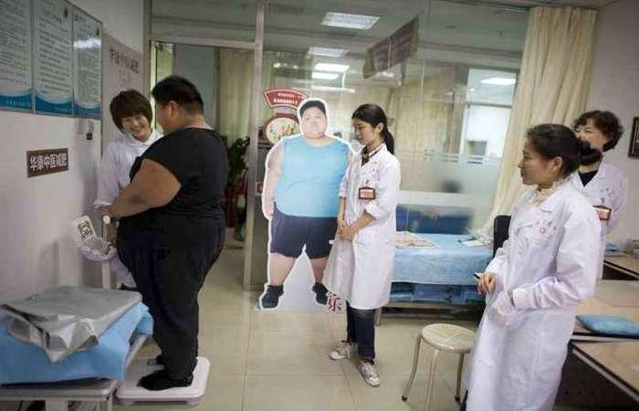 Observado por profissionais de saúde, adolescente chinês se pesa em um consultório de Pequim: demonstração de afeto é determinante para o paciente. foto: Alain Jocard/AFP - 12/4/19
