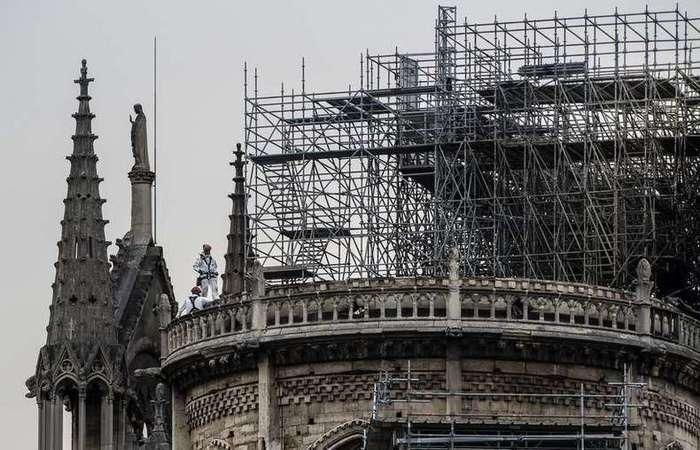 Trabalhadores escalam as torres de Notre-Dame para cobrir a catedral, devastada pelo fogo há uma semana - Foto: CHRISTOPHE ARCHAMBAULT / AFP